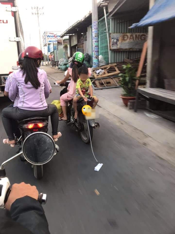 Mẹ để con trai ngồi ngược sau yên xe máy chơi đùa khi đi đường, mặc kệ xe tải chạy sát vách gây phẫn nộ - Ảnh 1.