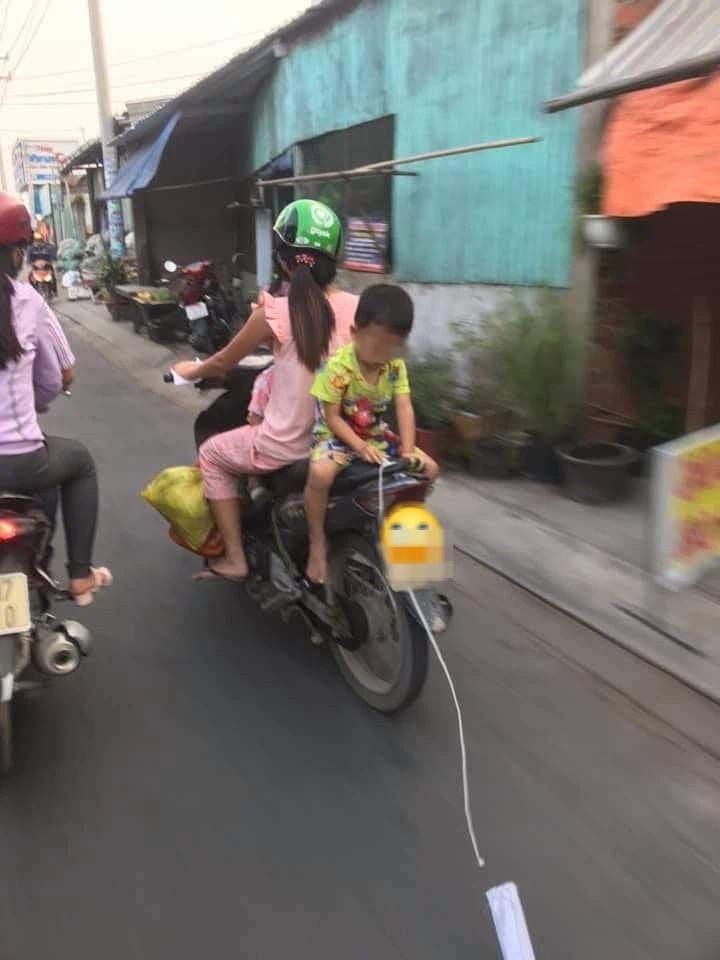 Mẹ để con trai ngồi ngược sau yên xe máy chơi đùa khi đi đường, mặc kệ xe tải chạy sát vách gây phẫn nộ - Ảnh 2.