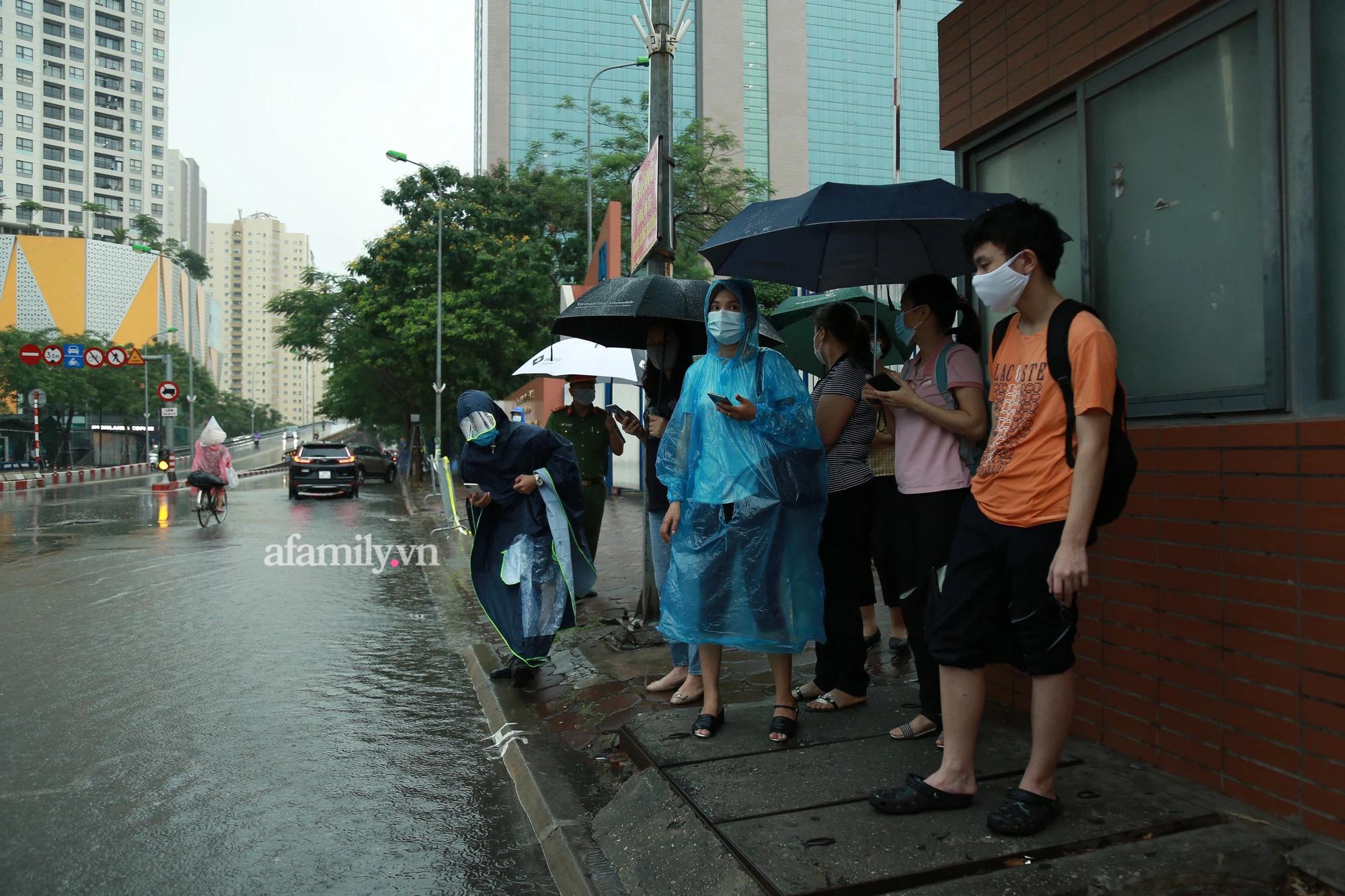 Mưa lớn như trút nước sáng 12/6, phụ huynh Hà Nội xách dép, đội mưa đưa con đi thi vào lớp 10 - Ảnh 2.
