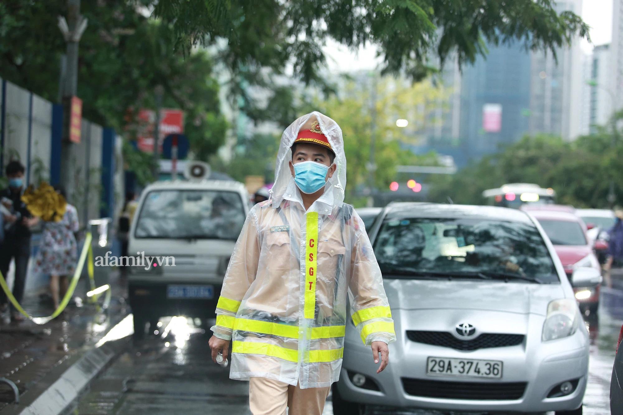 Mưa lớn như trút nước sáng 12/6, phụ huynh Hà Nội xách dép, đội mưa đưa con đi thi vào lớp 10 - Ảnh 13.