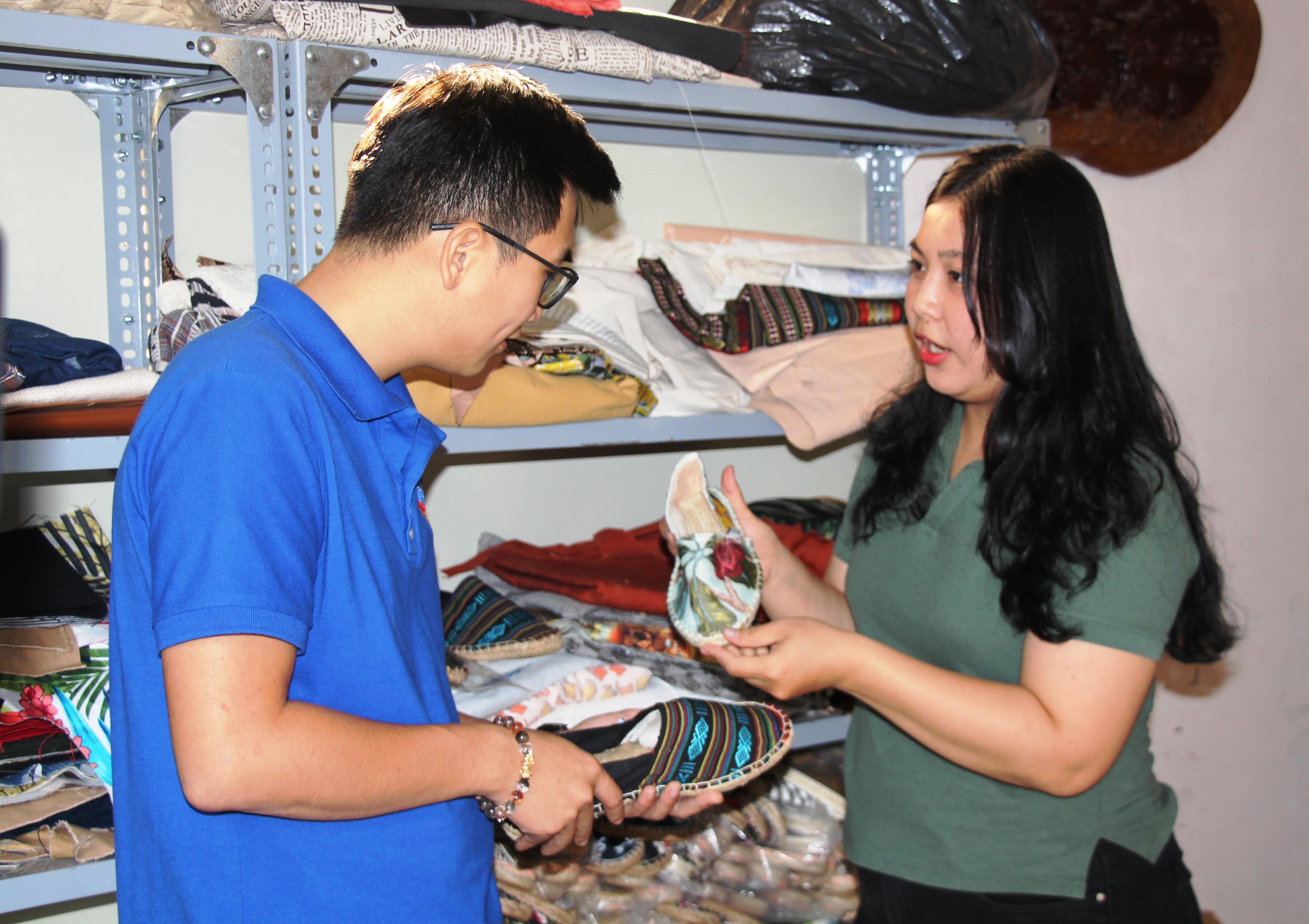 Chị Lưu Thúy Vân giới thiệu với khách hàng về sản phẩm giày cói
