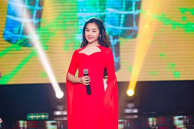 Cô bé diện áo dài màu đỏ mang đậm không khí xuân với kiểu dáng cách tân phần cổ cũng như cánh tay, trông không bị quá già dặn mà vẫn đảm bảo sự trang trọng.