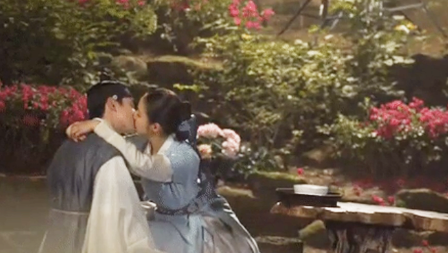Trên phim, nụ hôn lãng mạn ngọt ngào khi nữ chính quàng tay lên vai nam chính.