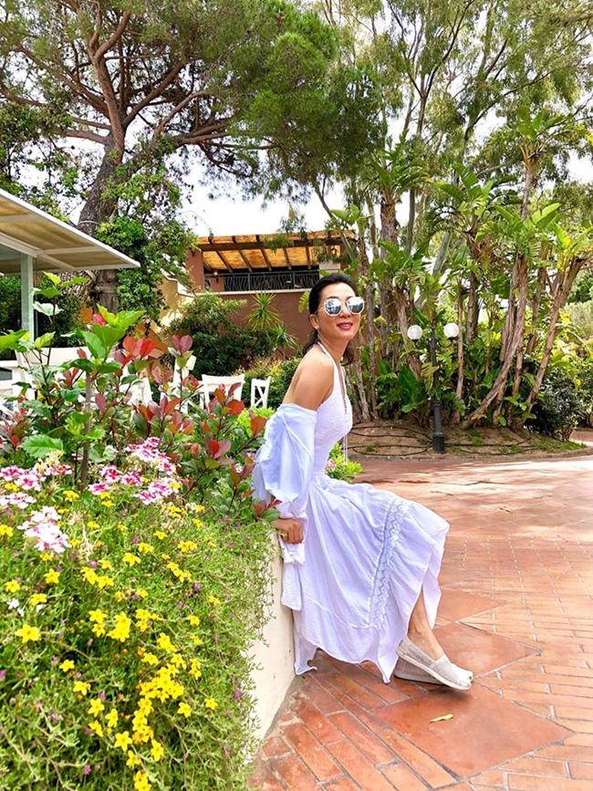 Nữ MC xinh đẹp ngôi thư giãn bên ngoài khuôn viên biệt thự.