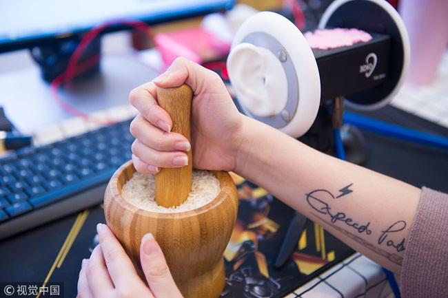 Cô gái cho chày vào cối đựng gạo để giã gạo tạo ra âm thanh trước micro và máy quay.