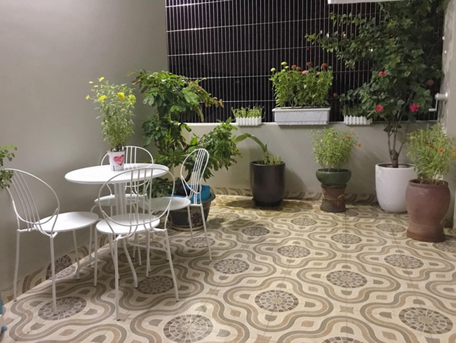 Ở ban công, hai vợ chồng Hoàng Linh - Mạnh Hùng trồng nhiều cây xanh và các loại hoa, đồng thời bố trí thêm bộ bàn ghế màu trắng để ngồi thư giãn, ngắm hoa, uống trà mỗi khi đêm về.