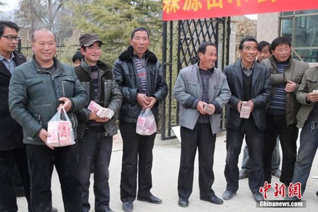 Năm 2014, 17 gia đình ở Lâm Thao, Định Tây, Cam Túc, Trung Quốc xếp hàng nhận túi tiền thưởng lớn từ cán bộ địa phương.