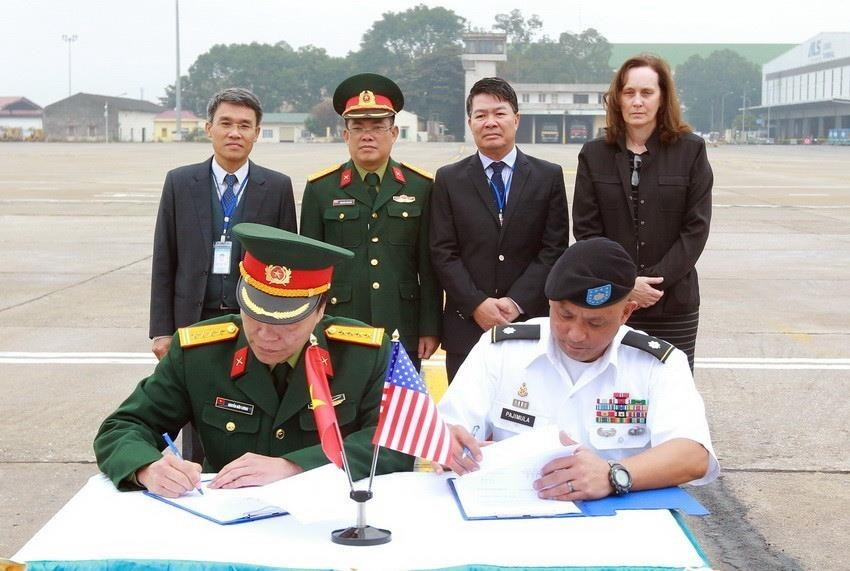 Representative of the Vietnamese Office For Seeking Missing Persons (VNOSMP) and representative of the US POW/MIA Accounting Agency (DPAA) sign a record of handing over 4 sets of remains of US soldiers during the 129th search, December 13, 2017, at Noi Bai International Airport (Hanoi) (Photo: VNA)