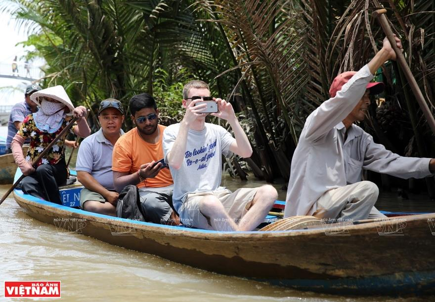 Foreign tourists explore the islet on small boats (Photo: VNA)