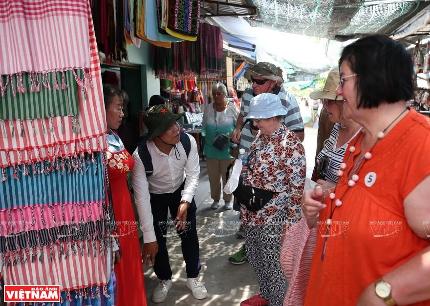Foreign tourists enjoy the local produce and souvenirs on Thoi Son islet (Photo: VNA)