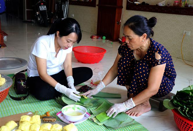 Green banana leaves are used to wrap the cake (Photo: VNA)