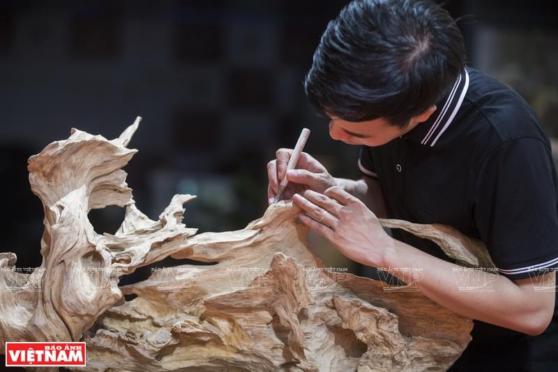 Tu uses different materials, notably wood, to make sculpture (Photo: VNA)