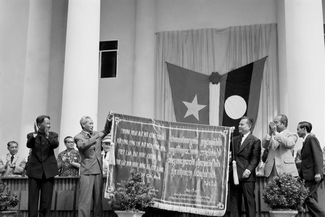 """Party General Secretary Le Duan and Prime Minister Pham Van Dong present the Lao Party Central Committee and Government a cloth canopy embroidered with President Ho Chi Minh's verses """"Vietnam and Laos, our two countries have a friendship deeper than the Hong Ha and Cuu Long rivers"""" during their official visit to Laos, July 15-18, 1977 (Photo: VNA)"""