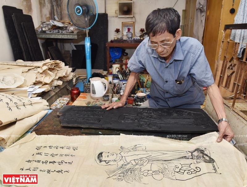 Artisan Nghien starts with woodblocks to print black basic shapes of the paintings and then draws the details (Photo: VNA)