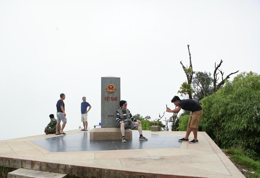 Tourists visit and pose for photos at Border Marker Zero (Photo: VNA)
