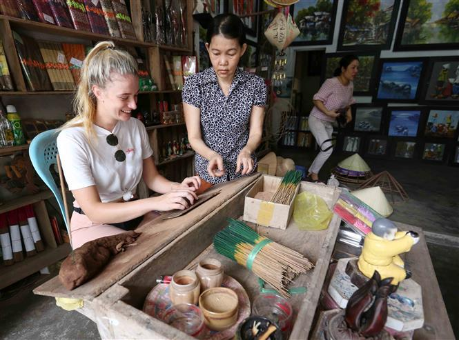 Tourists experience making incense in Thuy Xuan village (Photo: VNA)