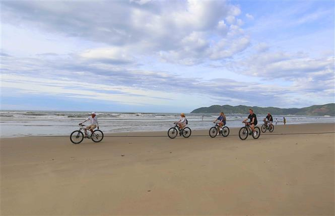 International visitors ride bicycle on Tan Canh Duong beach (Photo: VNA)