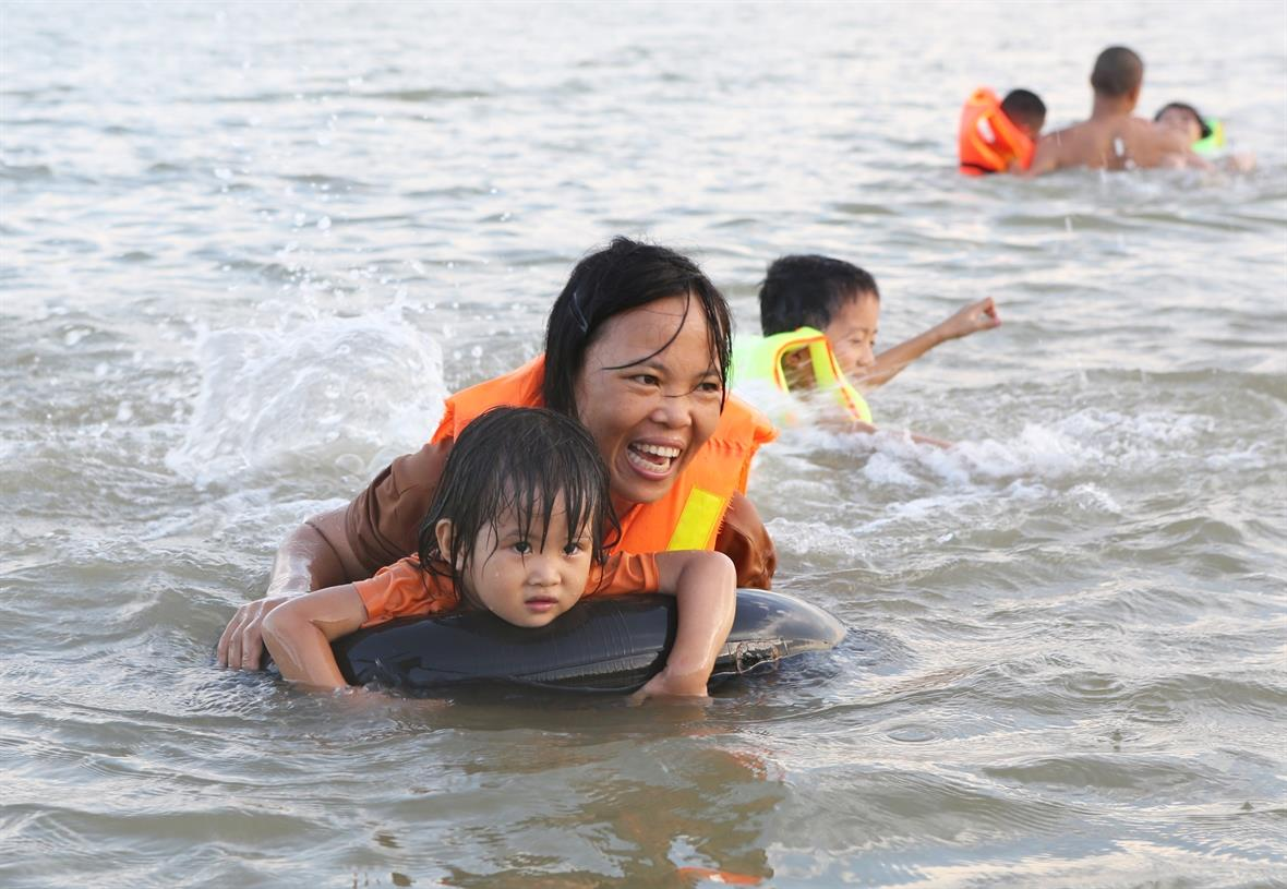 A mother is teaching her kid how to swim (Photo:VNA/VNP)