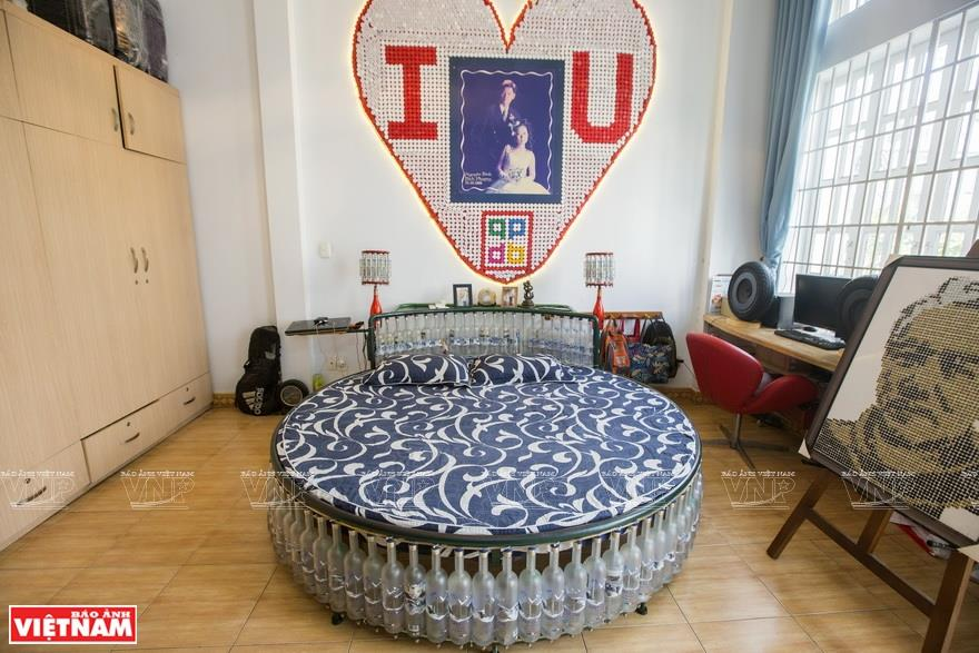 The bed in Binh's home was made from more than 200 bottles to celebrate the 15th anniversary of his wedding. It took him two years to collect bottles of the same size, model and color for making this bed (Photo: VNA)