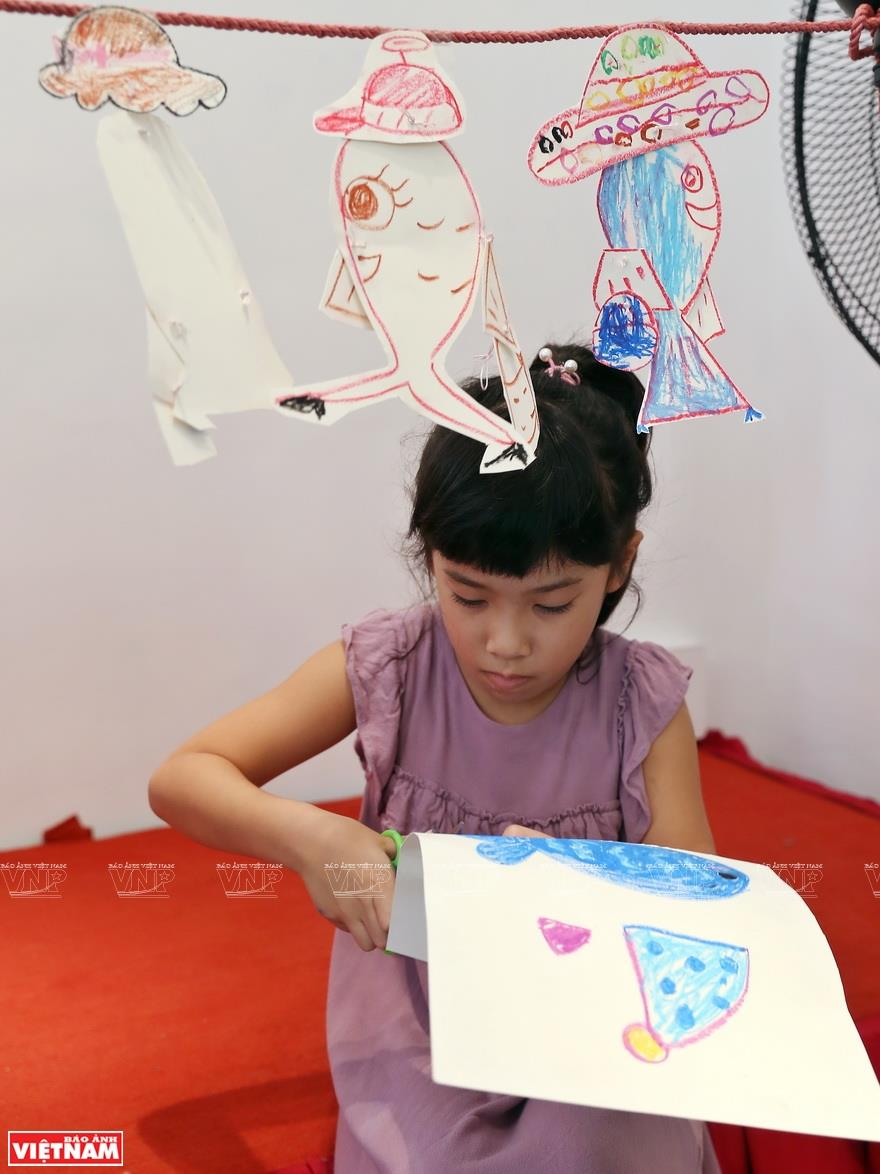 The images of a fish wearing a hat, carrying a handbag and going to shops in a department store help the children learn about life in a simple way (Photo: VNA)