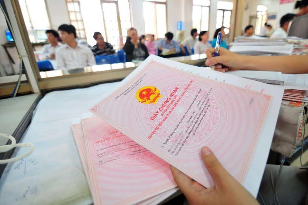 Bàn tay cầm sổ hồng, một tay cầm bút ghi chép, bóng nhiều người ngồi làm thủ tục sổ đỏ phía xa.