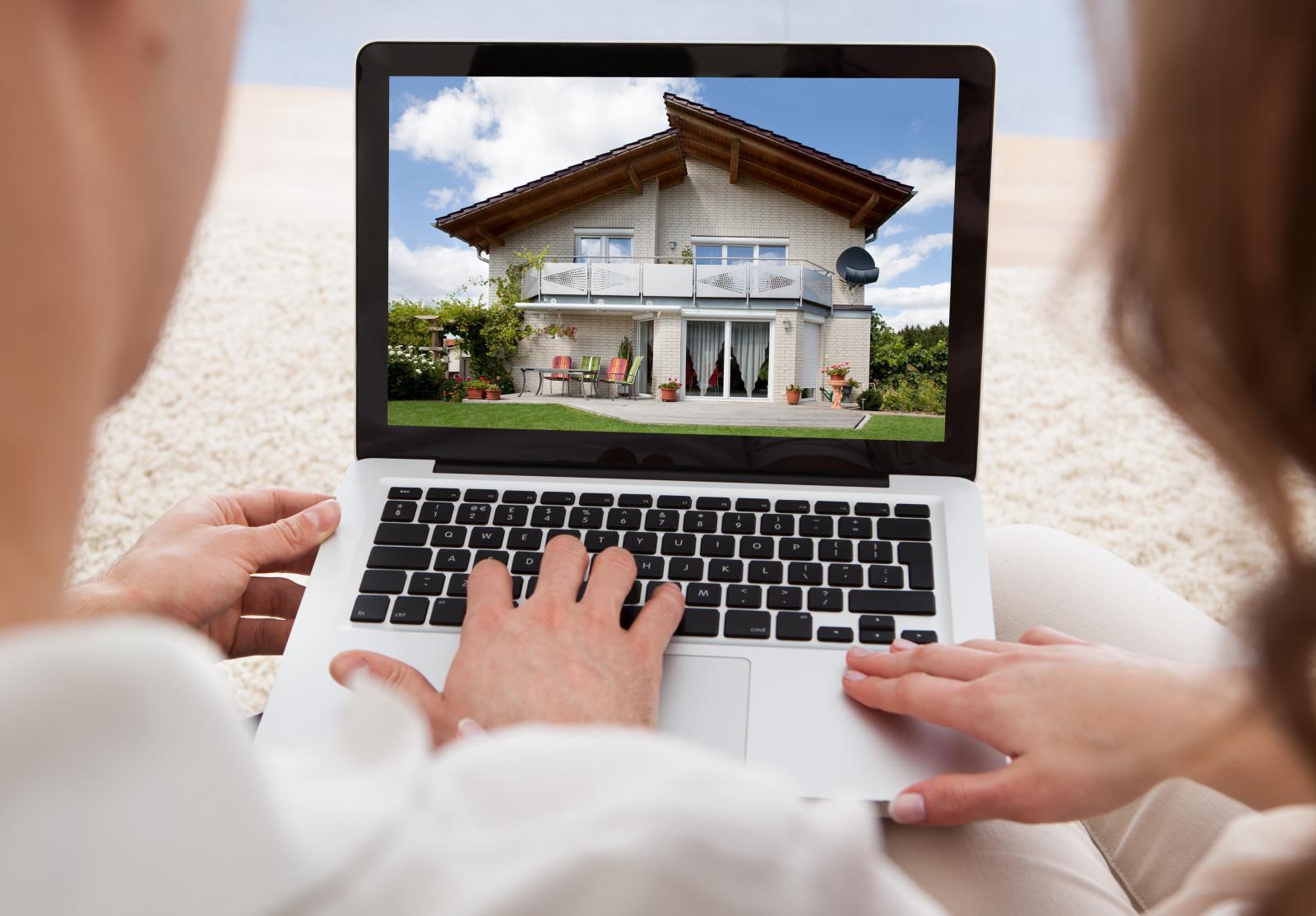 Hình ảnh 2 ngồi xem hình ảnh ngôi nhà trên chiếc máy tính xách tay