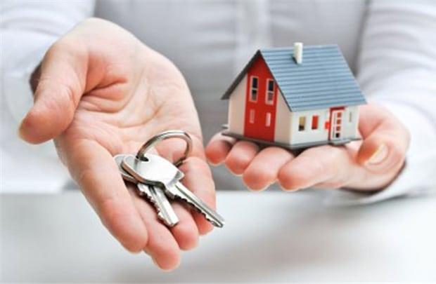 Một bàn tay chìa ra bên trên có chìa khóa, bàn tay còn lại cầm mô hình ngôi nhà.