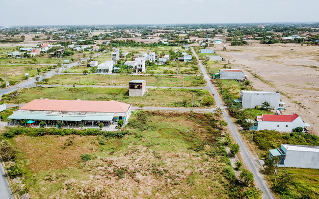 Ảnh chụp một khu đất trống cùng một số ngôi nhà và cây xanh