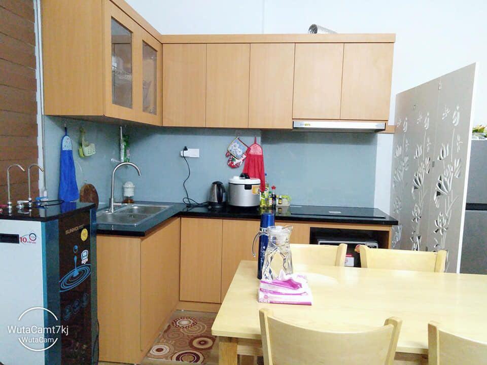 Căn bếp với chiếc bàn ăn nhỏ, bộ tủ bếp bằng gỗ màu vàng nhạt, máy lọc nước đặt cạnh bàn bếp
