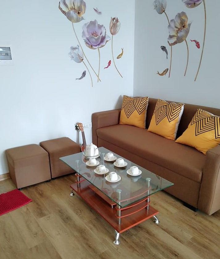 Một góc phòng khách với bộ ghế sofa màu nâu, chiếc bàn mặt kính có bộ ấm chén màu trắng, bên cạnh là cây đàn ghi ta
