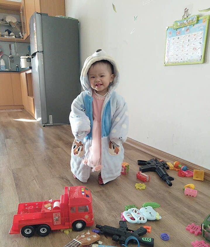 Một bé gái đứng cười bên cạnh đống đồ chơi, phía sau là một góc căn bếp với chiếc tủ lạnh