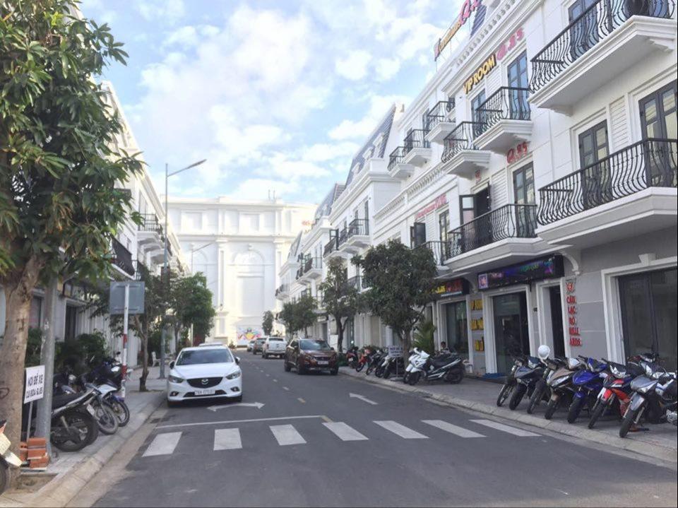Một dãy nhà phố thương mại, bên dưới là đường, nhiều xe máy trên vỉa hè, ô tô chạy trên đường