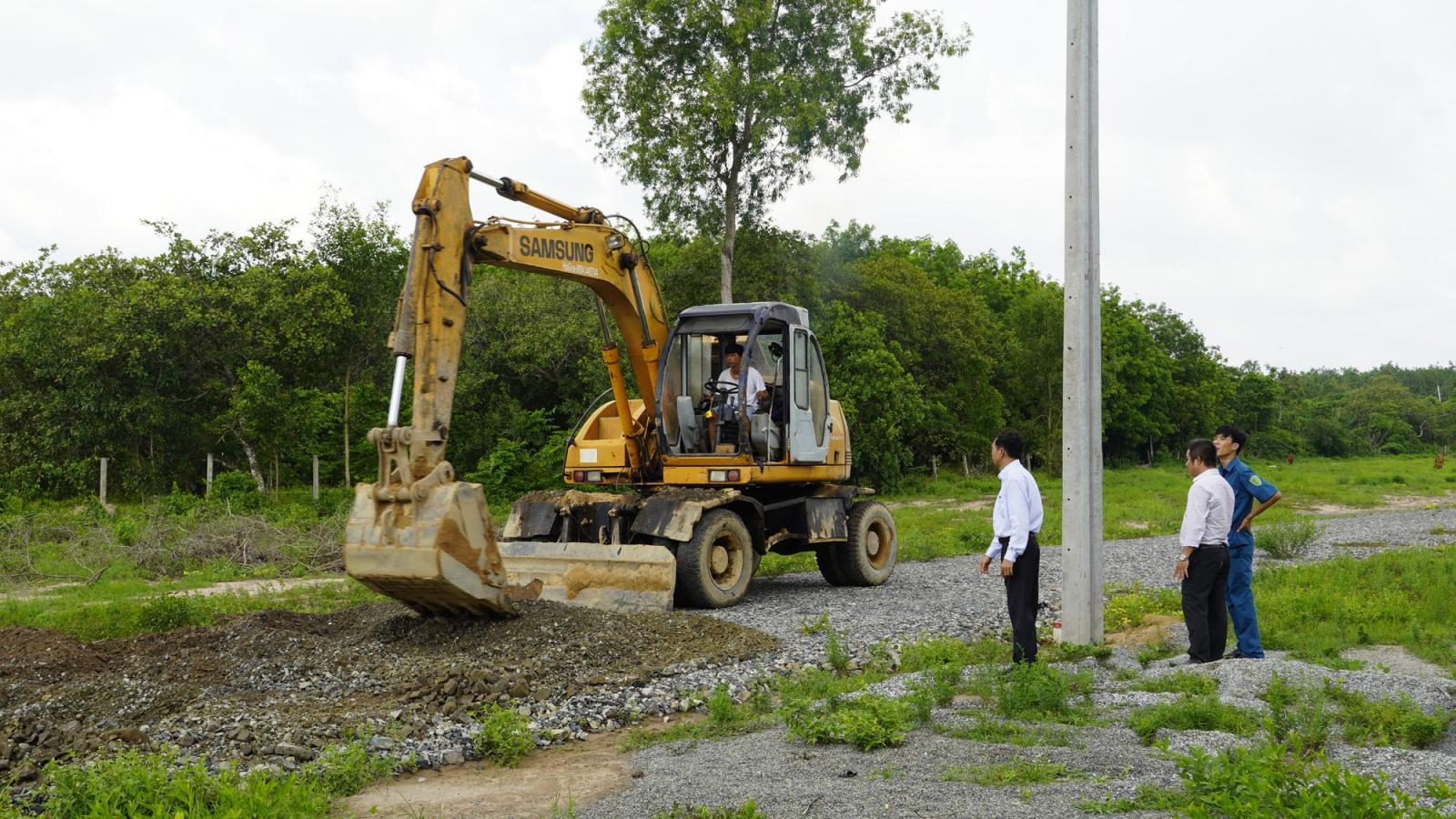 Máy xúc phá dỡ đường trong dự án đất nông nghiệp phân lô, ba người đàn ông đứng xem.
