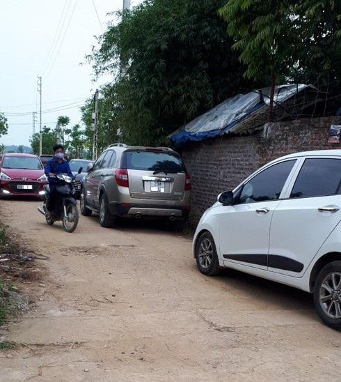 Nhiều ô tô đậu trên một con đường nhỏ trong làng ở Hòa Lạc, nơi xảy ra đợt sốt đất giữa dịch Covid-19.