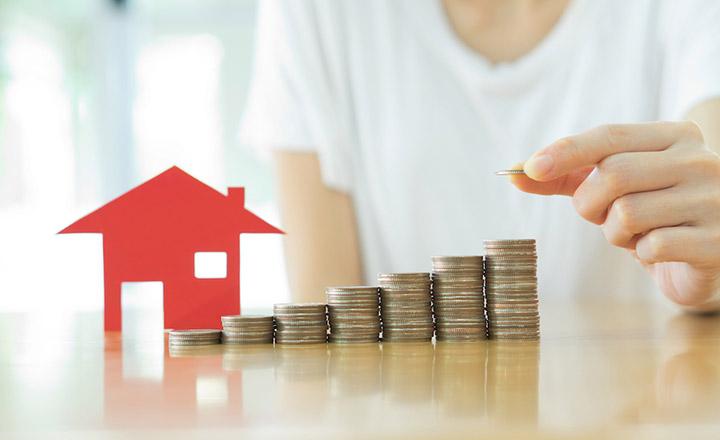 1 ngôi nhà và phía trước là những chồng tiền xu giá trị lớn dần