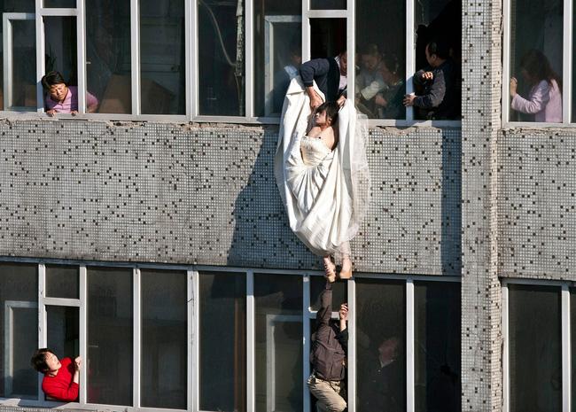 Cô gái mặc váy cưới nhảy khỏi tòa nhà, cuộc giải cứu nghẹt thở trong 54 giây và bức ảnh đạt giải thưởng gây xúc động mạnh - Ảnh 2.