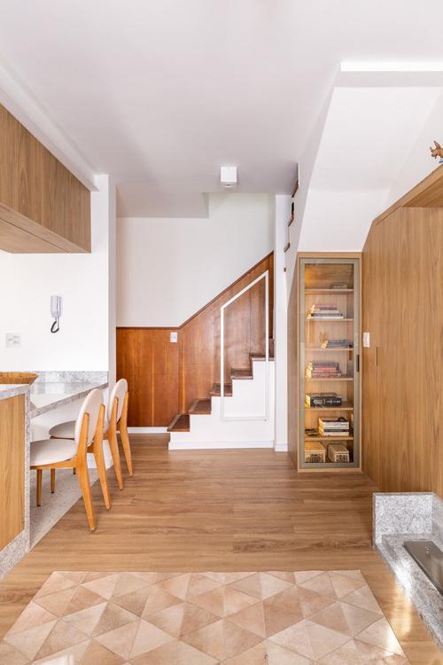 Phía dưới cầu thang dẫn lên tầng một được đặt kệ sách. Phòng ngủ bên cạnh kệ sách gần như vô hình vì cánh cửa phòng trùng khớp màu tường gỗ.