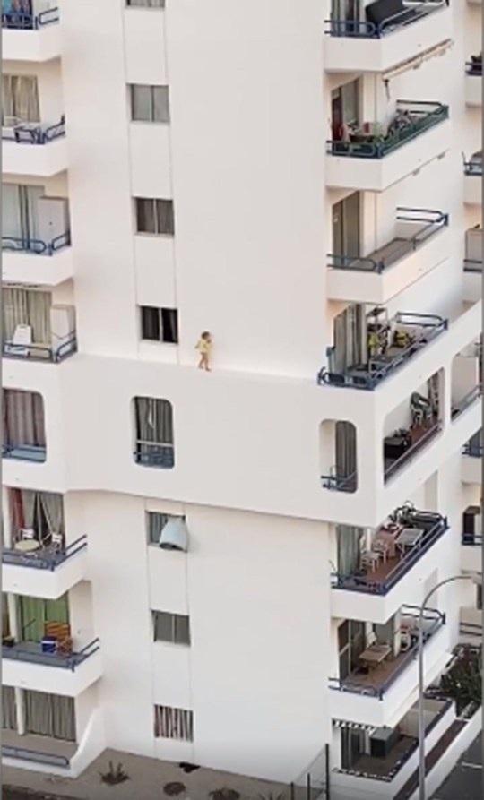 Thót tim xem em bé chạy tung tăng trên rìa tường tầng 4 tòa nhà cao tầng - 1