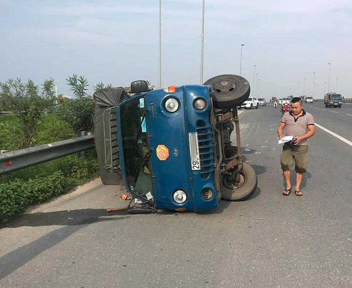 Đánh lái gấp để tránh taxi chạy ẩu, xe tải lật nghiêng xuống đường - 1