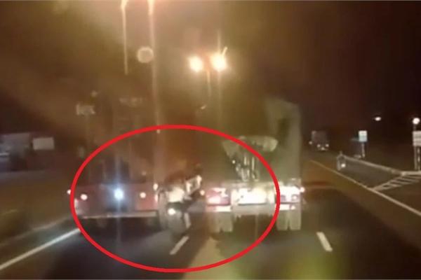 Cặp đôi liều mạng phóng xe máy chen vào giữa 2 xe tải như phim hành động