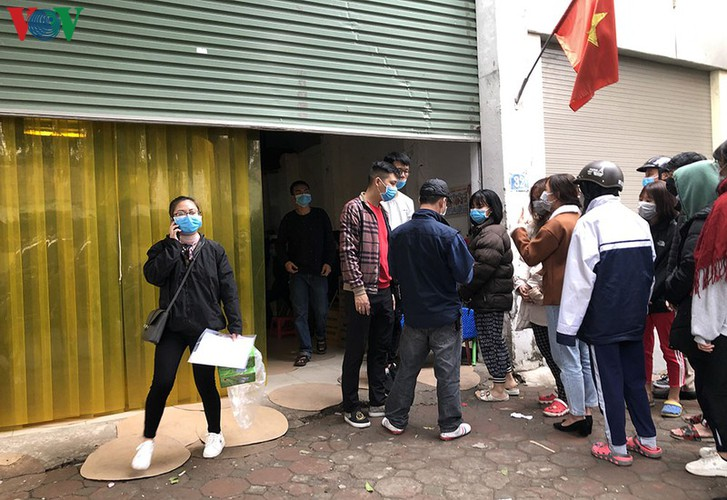people queue up to buy medical masks at standard price hinh 2