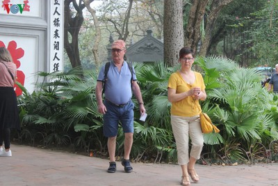 Foreign tourists in Hanoi wander streets without face masks