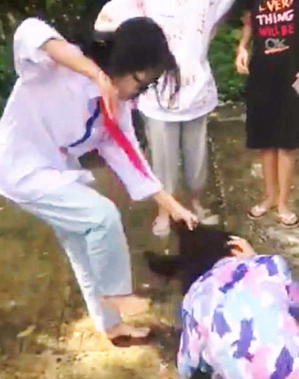 Bé gái (áo hoa) bị bạn xúm lại đánh hội đồng. Ảnh cắt từ clip