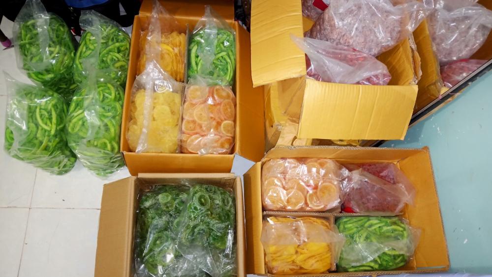 Một điểm đang sang chiết mứt từ các thùng mứt không có nhãn mác sang các hộp, túi mứt được in tiếng Thái Lan