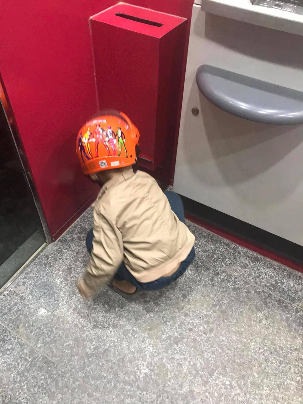 Cậu bé loay hoay nhặt những tờ biên lai dưới sàn ở một máy ATM. Ảnh từ Facebook