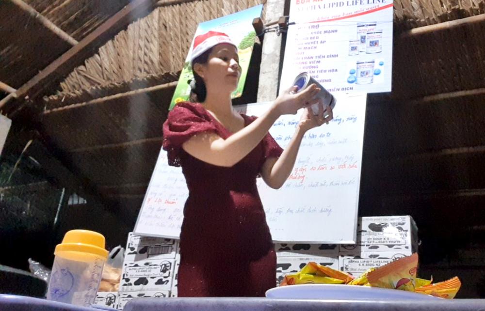 Bà Như Anh, người được cho là tuyến trên tại điểm bán sữa, đang hướng dẫn mọi người kiểm tra sữa thật