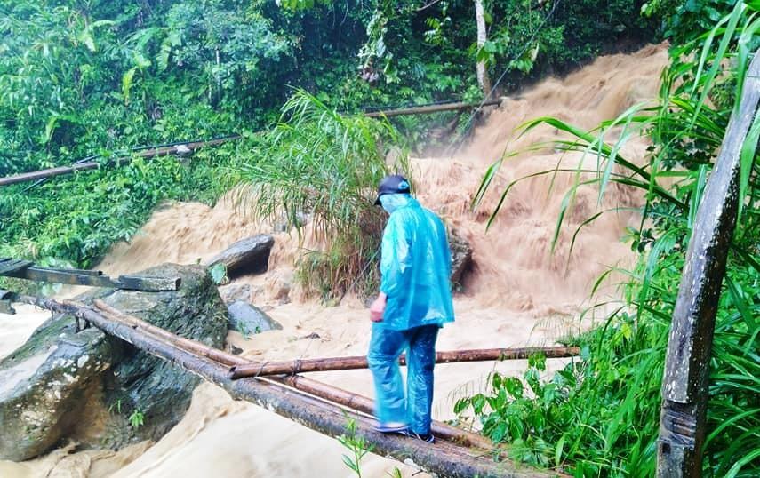 Một người dân cố gắng vượt lũ bằng cầu tạm tại xã Ch'ƠM (Tây Giang). Ảnh: Facebook Đ.Đ.N