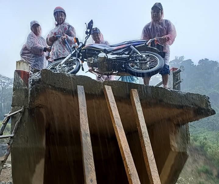 """Nhóm người vùng cao dùng dây dù và vài thanh gỗ để kéo xe máy lên chiếc """"cầu cụt"""" sau phút giây sinh tử. Ảnh: facebook Chip So"""