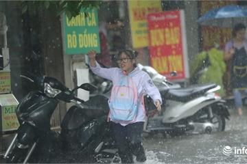 """Hà Nội: Mưa lớn đúng lúc nghỉ trưa, nhiều người phải """"rẽ sóng"""" nước về nhà"""