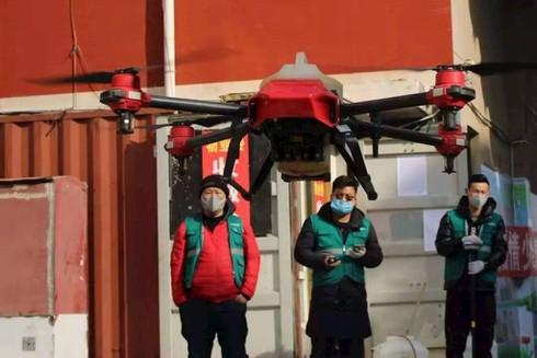 Trung Quốc dùng drone phun thuốc khử trùng, chiếu sáng công trường bệnh viện dã chiến - ảnh 1